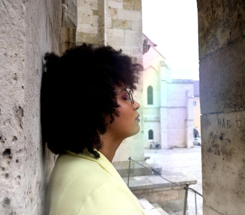 Jade lehnt an eine Steinwand. Die Augen geschlossen. Vor ihrem Gesicht ein Regenbogen.