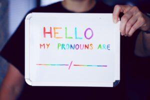 Ein Mensch hält ein Schild hoch. In Regenbogenschrift steht darauf: Hello My Pronouns Are